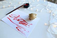 Tarjeta de letras con días de fiesta del texto en color del escarlata en el shee blanco Fotos de archivo libres de regalías