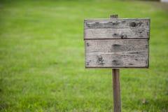 Tarjeta de madera en hierba Fotos de archivo libres de regalías