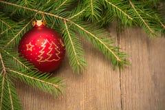 Tarjeta de Navidad con el árbol de abeto y bola roja de la Navidad en vagos de madera foto de archivo