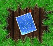 Tarjeta de Navidad con el abeto verde en la madera Imagenes de archivo