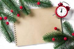 Tarjeta de Navidad con el cuaderno y el reloj vacíos Fotos de archivo