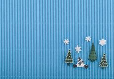 Tarjeta de Navidad con el muñeco de nieve, los árboles y los copos de nieve en el papel acanalado azul Foto de archivo libre de regalías