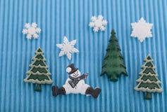 Tarjeta de Navidad con el muñeco de nieve, los árboles y los copos de nieve en el papel acanalado azul Imagen de archivo libre de regalías