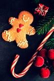 Tarjeta de Navidad con el regalo de la Navidad, galleta del hombre de pan de jengibre, abeto Fotografía de archivo libre de regalías