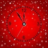 Tarjeta de Navidad con el reloj en un fondo rojo Imagenes de archivo