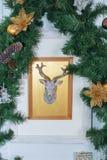 Tarjeta de Navidad con el reno y el árbol verde Imagenes de archivo