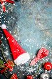 Tarjeta de Navidad con el sombrero de Papá Noel, la nieve y la decoración roja del invierno en fondo azul del vintage Fotografía de archivo libre de regalías