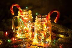 Tarjeta de Navidad con el tarro de la guirnalda y el bastón de caramelo que brillan intensamente Fotografía de archivo libre de regalías
