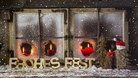Tarjeta de Navidad con el texto alemán en rojo con las velas Fotos de archivo