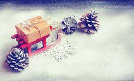 Tarjeta de Navidad con el trineo rojo, caja de regalo, primer Imagen de archivo