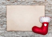 Tarjeta de Navidad con la hoja de papel y el calcetín rojo Fotografía de archivo libre de regalías