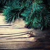 Tarjeta de Navidad con la rama de árbol de abeto sobre fondo de madera con Foto de archivo