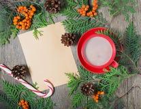 Tarjeta de Navidad con la taza de cacao, de árbol de abeto, de pinecones y de serbal Imagenes de archivo