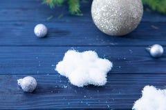 Tarjeta de Navidad con las bolas y las estrellas de plata en TA de madera azul Imagen de archivo libre de regalías