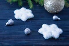 Tarjeta de Navidad con las bolas y las estrellas de plata en TA de madera azul Imágenes de archivo libres de regalías