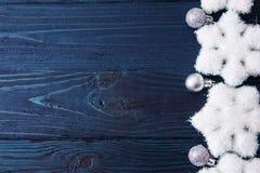 Tarjeta de Navidad con las bolas y las estrellas de plata en TA de madera azul Fotos de archivo