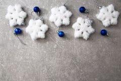 Tarjeta de Navidad con las bolas y las estrellas de plata en TA de madera azul Foto de archivo