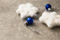 Tarjeta de Navidad con las bolas y las estrellas de plata en TA de madera azul Fotografía de archivo