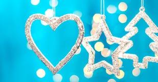 Tarjeta de Navidad con las decoraciones de la Navidad en un fondo azul chispeante Imagen de archivo
