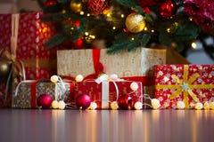 Tarjeta de Navidad con las decoraciones, los regalos y las luces festivos sobre copyspace colorido del fondo Fotografía de archivo