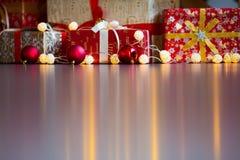 Tarjeta de Navidad con las decoraciones, los regalos y las luces festivos sobre copyspace colorido del fondo Imágenes de archivo libres de regalías
