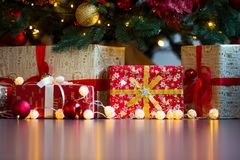 Tarjeta de Navidad con las decoraciones, los regalos y las luces festivos sobre copyspace colorido del fondo Imagen de archivo
