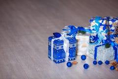 Tarjeta de Navidad con las decoraciones, los regalos y las luces festivos sobre el fondo Copyspace del piso Fotografía de archivo libre de regalías