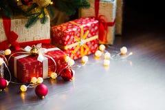 Tarjeta de Navidad con las decoraciones, los regalos y las luces festivos sobre el fondo de madera Copyspace Imagen de archivo