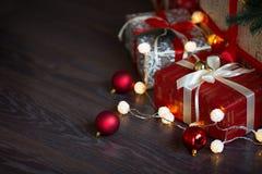 Tarjeta de Navidad con las decoraciones, los regalos y las luces festivos sobre el fondo de madera Copyspace Foto de archivo