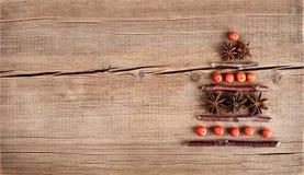 Tarjeta de Navidad con las decoraciones naturales en fondo de madera Fotos de archivo libres de regalías