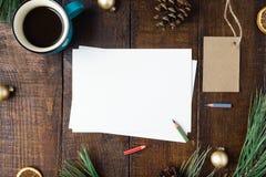 Tarjeta de Navidad con las decoraciones y café de la taza en la tabla de madera Imagen de archivo