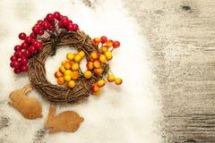 Tarjeta de Navidad con las liebres y la pequeña guirnalda de la corteza de abedul en un fondo de madera Imagen de archivo libre de regalías