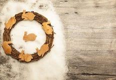 Tarjeta de Navidad con las liebres y la pequeña guirnalda de la corteza de abedul en un fondo de madera Foto de archivo