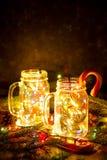 Tarjeta de Navidad con las luces y el bastón de caramelo que brillan intensamente en los tarros de cristal en fondo oscuro Fotografía de archivo libre de regalías