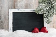 Tarjeta de Navidad con los corazones rojos y la pizarra en blanco Foto de archivo