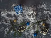 Tarjeta de Navidad con los juguetes decorativos de la Navidad con nieve fuerte en el fondo de madera negro imagenes de archivo