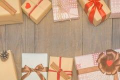 Tarjeta de Navidad con los presentes, el árbol de abeto y los conos del pino en de madera foto de archivo