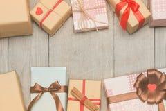 Tarjeta de Navidad con los presentes, el árbol de abeto y los conos del pino en de madera imágenes de archivo libres de regalías