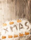 Tarjeta de Navidad con Navidad de la inscripción con los pequeños conejos de la Navidad de la corteza de abedul en la nieve en un Fotografía de archivo libre de regalías
