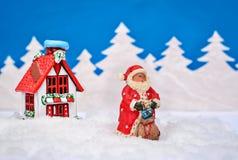 Tarjeta de Navidad con Papá Noel y una casa en el bosque del invierno Imagen de archivo