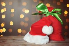 Tarjeta de Navidad con un bolso rojo lleno de regalos y de un sombrero de Santa Claus en una tabla de madera Guirnalda luminosa e Fotos de archivo libres de regalías