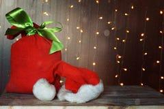 Tarjeta de Navidad con un bolso rojo lleno de regalos y de un sombrero de Santa Claus Guirnalda luminosa en el fondo Fotografía de archivo