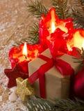 Tarjeta de Navidad Cuatro velas rojas con el regalo de la Navidad Fotos de archivo