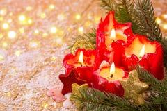 Tarjeta de Navidad Cuatro velas rojas con el regalo de la Navidad Fotografía de archivo