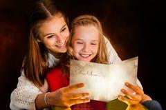 Tarjeta de Navidad de la lectura de la muchacha a la hermana Fotografía de archivo