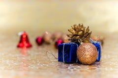 Tarjeta de Navidad del concepto Bolas de las decoraciones de la Navidad, caja de regalo, cascabel en fondo de oro Imagen de archivo
