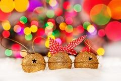 Tarjeta de Navidad del saludo con el oro Jingle Bells en el fondo colorido de Bokeh Imagen de archivo