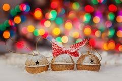 Tarjeta de Navidad del saludo con el oro Jingle Bells en el fondo colorido de Bokeh Fotografía de archivo libre de regalías