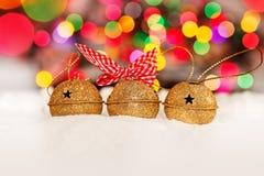 Tarjeta de Navidad del saludo con el oro Jingle Bells en el fondo colorido de Bokeh Fotos de archivo libres de regalías