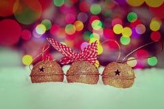 Tarjeta de Navidad del saludo con el oro Jingle Bells en el fondo colorido de Bokeh Imagen entonada Fotografía de archivo